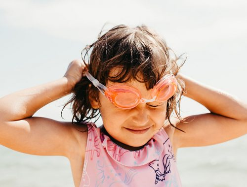 Girl struggling to put on goggles