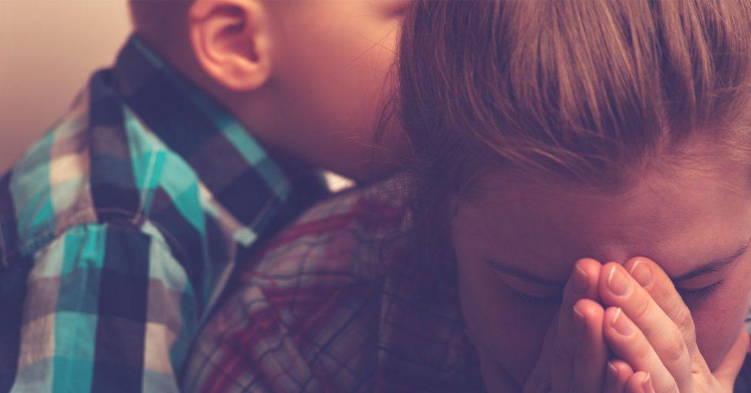 Boy comforting praying mom